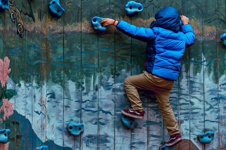 Kid rock climbing on a wall