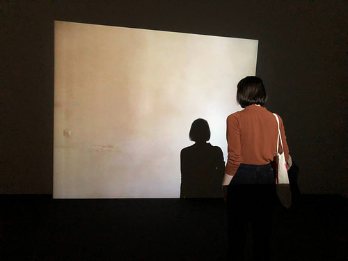 Woman standing in front of projector screen