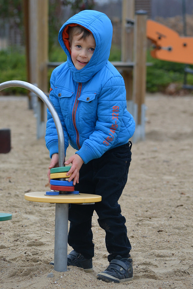 Kid playing with poles and rings