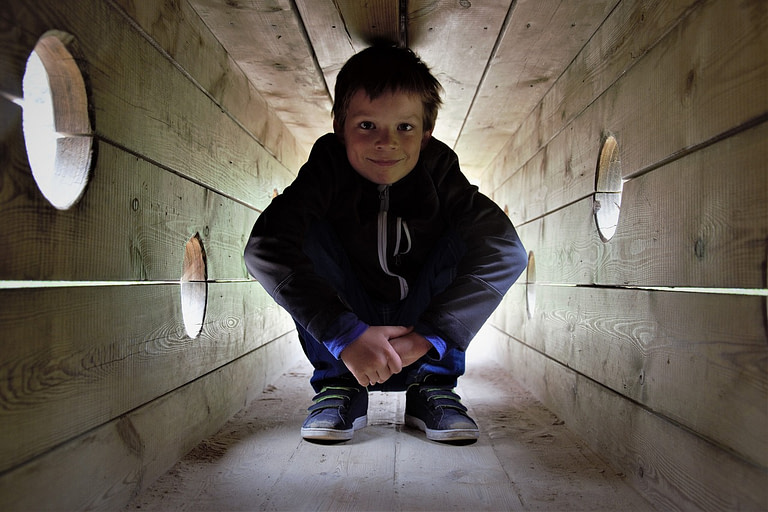 Kid squatting a wooden tunnel