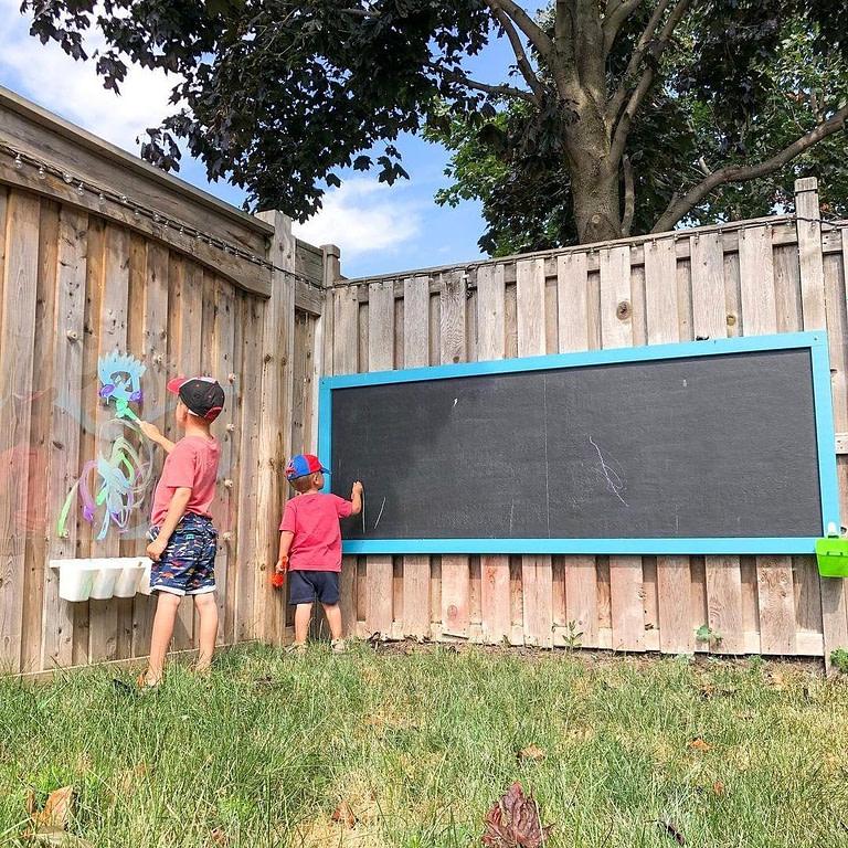 Kids writing on a chalkboard outdoors