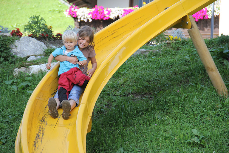 Kids playing on a yellow slide